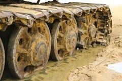 Gammal järnlarv i våt sand Rostiga stålhjul och larvband av en stor bulldozer, behållare, grävskopa, i fuktig sand och Arkivbild