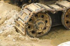 Gammal järnlarv i våt sand Rostiga stålhjul och larvband av en stor bulldozer, behållare, grävskopa, i fuktig sand och Arkivbilder
