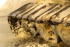 Gammal järnlarv i våt sand Rostiga stålhjul och larvband av en stor bulldozer, behållare, grävskopa, i fuktig sand och Royaltyfri Foto