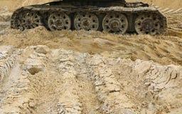 Gammal järnlarv i våt sand Rostiga stålhjul och larvband av en stor bulldozer, behållare, grävskopa, i fuktig sand och Royaltyfri Fotografi