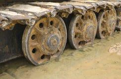 Gammal järnlarv i våt sand Rostiga stålhjul och larvband av en stor bulldozer, behållare, grävskopa, i fuktig sand och Arkivfoton