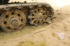 Gammal järnlarv i våt sand Rostiga stålhjul och larvband av en stor bulldozer, behållare, grävskopa, i fuktig sand och Royaltyfria Bilder