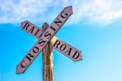 Gammal järnvägkorsning tecken mot blå himmel royaltyfri foto
