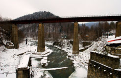 Gammal järnvägsbro över den snabba bergfloden Arkivfoto
