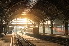 Gammal järnvägsstation med ett drev och en lokomotiv på plattformen som väntar på avvikelse Aftonsolskenstrålar i rökbågar arkivbilder