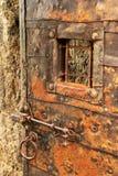 Gammal järn-klädd dörr med det grillade fönstret, stånglåset och cirkelhandtaget Royaltyfria Bilder
