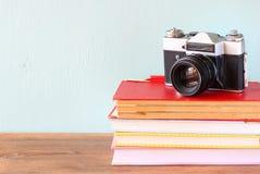 Gammal kamera över bunt av böcker royaltyfri fotografi