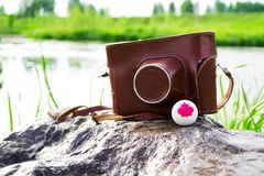 Gammal kamera i ett brunt fall och en boll med symbolet av Kanada Arkivfoton