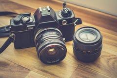 gammal kamera med hans andra lins i mitt av en brun träbakgrund Royaltyfria Bilder