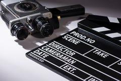 Gammal kamera med två linser och en filmclapperboard royaltyfria foton
