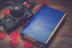 gammal kamera och en anteckningsbok som reser, och kronblad av blommor i garnering royaltyfria foton