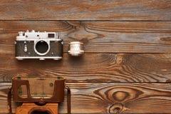 Gammal kamera och lins för tappning på träbakgrund Fotografering för Bildbyråer