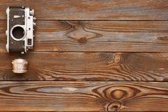 Gammal kamera och lins för tappning på träbakgrund Arkivbild