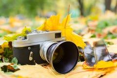 Gammal kamera på gula höstsidor med gamla negationer royaltyfri bild