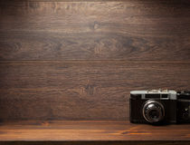 Gammal kamera på hyllaväggträ royaltyfri bild