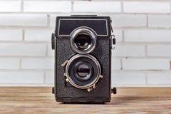 Gammal kamera som retuscherar tappning på trätabellen Retro kamera med två linser Royaltyfri Bild