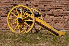 Gammal kanon framme av en tegelstenvägg Arkivfoto