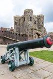 Gammal kanon som framme ses av den medeltida slotten i råg, UK Royaltyfria Bilder