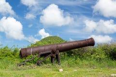 Gammal kanon som rostar på St karibiska Martin Arkivfoto