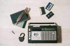 Gammal kassettbandspelare, tangent, lås, böcker och fjäder på trä Royaltyfria Foton