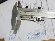 Gammal klämma och mikrometer på tekniska teckningar Arkivfoto