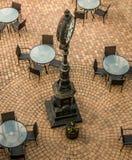 Gammal klocka i en kaféfyrkant med trottoar Arkivfoton