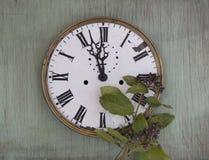 Gammal klocka på den gröna wood bakgrunden Bakgrund för nytt år med växter och lilabär Nya sidor och purpurfärgade bär Vinta Arkivfoton