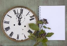 Gammal klocka på den gröna wood bakgrunden Bakgrund för nytt år med växter och lilabär Nya sidor och purpurfärgade bär Vinta Royaltyfri Bild