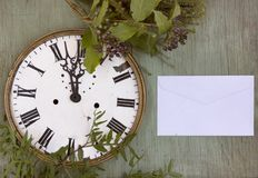 Gammal klocka på den gröna wood bakgrunden Bakgrund för nytt år med växter och lilabär Nya sidor och purpurfärgade bär Vinta Royaltyfria Bilder