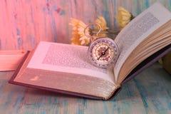 Gammal kompass på öppen gammal text Fotografering för Bildbyråer