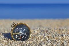 Gammal kompass på stranden Arkivfoton