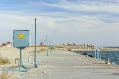Gammal konkret bana i sjösidan med en linje av rostig transforme arkivfoto