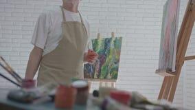 Gammal konstnär som arbetar i atelier med färgrika målarfärger lager videofilmer