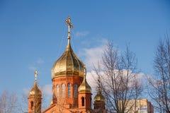 Gammal kristen kyrka för röd tegelsten med guld- och förgylld kupolagai arkivbild