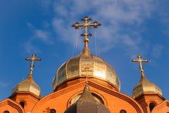 Gammal kristen kyrka för röd tegelsten med guld- och förgyllda kupolagains royaltyfri bild