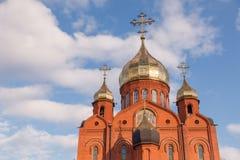 Gammal kristen kyrka för röd tegelsten med guld- och förgyllda kupolagains royaltyfri foto
