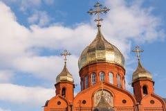 Gammal kristen kyrka för röd tegelsten med guld- och förgyllda kupolagains arkivbilder