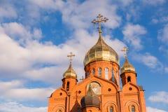 Gammal kristen kyrka för röd tegelsten med guld- och förgyllda kupolagains arkivbild