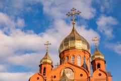 Gammal kristen kyrka för röd tegelsten med guld- och förgyllda kupolagains royaltyfria bilder