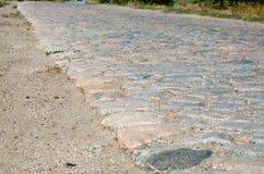 Gammal kullerstenväg som stenläggas med stenar Royaltyfri Bild