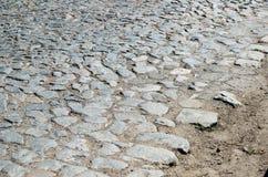 Gammal kullerstenväg som stenläggas med stenar Arkivfoto