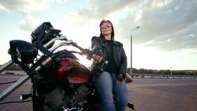 Gammal kvinna för cyklist i läderomslag och handskar som sitter på hans kalla motorcykel Kvinnan har runda exponeringsglas och et