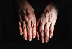 Gammal kvinna, grandmoterhänder som isoleras på svart som evakueras arkivfoto