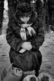 Gammal kvinna i päls som säljer bär i vinter Arkivfoto
