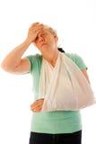Gammal kvinna med den brutna handleden i gips Arkivfoto
