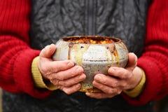 Gammal kvinna med den gamla järnkrukan med havregröt i henne händer Traditionell rysk mat Royaltyfri Foto