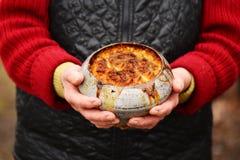 Gammal kvinna med den gamla järnkrukan med havregröt i henne händer Traditionell rysk mat Royaltyfri Bild