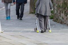 Gammal kvinna med en apparat på hjul för en gå på gatan arkivfoto