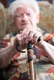 Gammal kvinna med hennes händer på en rotting Arkivbild