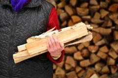 Gammal kvinna med vedträ i händerna i byn Fotografering för Bildbyråer